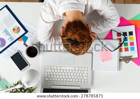 Tired female employee at workplace in office taking nap. Sleepy worker early in the morning after late night work. Creative person (designer or artist) in despair caused by deadline concept