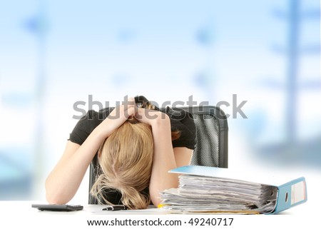 Tired female executive filling out tax forms while sitting at her desk.