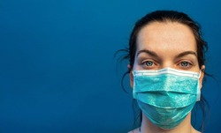 Tired female nurse, wearing a turquoise surgical mask, exhausted after a difficult day in the hospital helping  COVID-19, corona virus, patients. Standing against a blue wall with slogan, copy space.