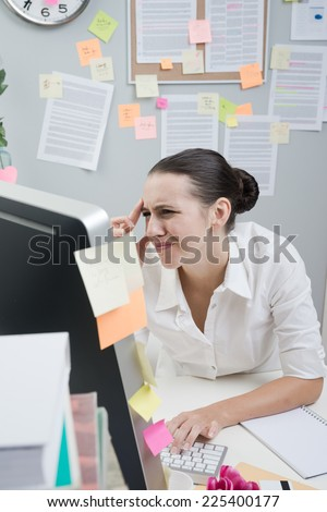 Tired female white collar working at computer with eye pain touching her temples.