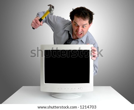 Tired, freaked-out business man preparing to smash a computer monitor with a hammer.
