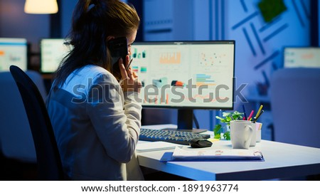 Tired freelancer talking at smartphone with colleague working overtime sitting at desk in business office late at night resolving financial problems. Busy employee using modern technology network Foto stock ©