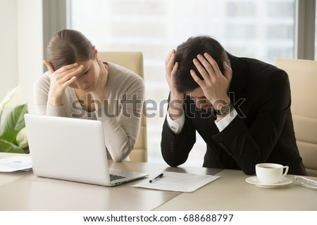 Tired frustrated business people feeling stressed, upset executives sitting near laptop, holding head in hands, worried about business problem failure, depressed by bad news, company bankruptcy