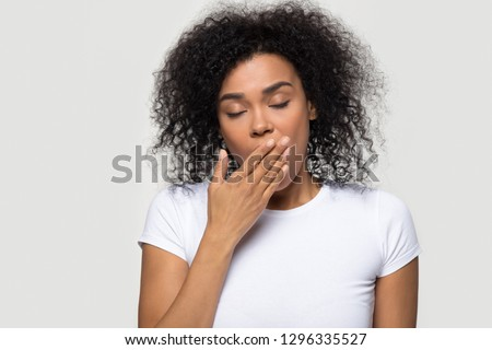 Tired funny drowsy african american woman yawning isolated on white grey studio background, sleepy inattentive deprived black female feeling somnolent lazy bored gaping suffering from lack of sleep