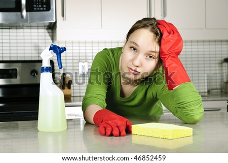 Tired girl doing kitchen cleaning chores with rubber gloves