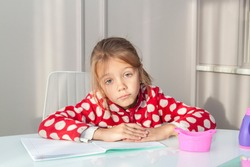 tired girl has her hands folded on school notebook and looks at camera, studying at home at table. child is doing homework. Difficult reading and writing task for elementary school