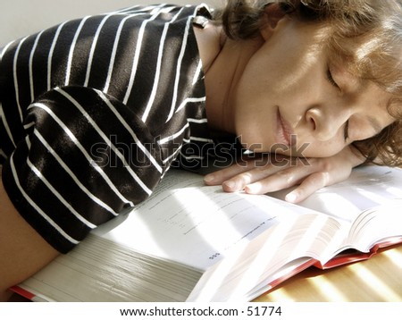 Tired girl is sleeping on her book