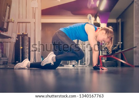 Tired girl portrait with white hair, squatting and pushing to train her legs on leg press machine in modern gym. Healthy lifestyle concept. stretching of the feet. blonde is on her knees