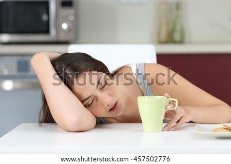 Tired girl sleeping on the table of the kitchen at breakfast