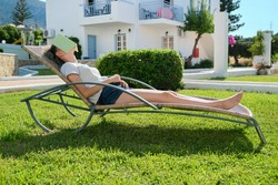 Tired girl sleeping with book on her face. Teen girl lying on garden lounger on lawn near house, sunny summer day