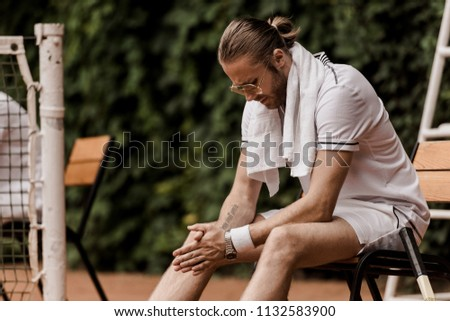 tired handsome tennis player sitting on chair at tennis court #1132583900