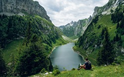 Tired hiker drinks water from a bottle with beautiful view of the third largest mountain lake he canton of Appenzell. Lake Fahlensee or Falensee in Zwinglipass, Switzerland. Travel and Adventure life
