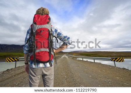 Tired Hiker , with a defeated pose, looks across a bridge at the bus home, leaving from the middle of nowhere.
