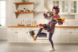 Tired housewife cooking food and carrying lots of stuff. Frail slim young woman making meal at home, holding multiple heavy cooking pots and kitchen saucepans, balancing cutting boards with vegetables