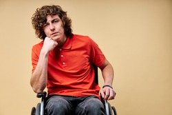 tired invalid man want to recover and get back on feet, sits on wheelchair exhausted looking at camera, leaning on one arm. isolated