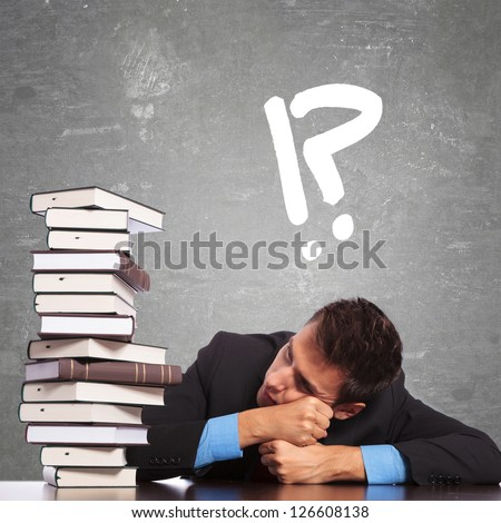 tired law student looking at a big pile of books he has to learn or read to pass the exam