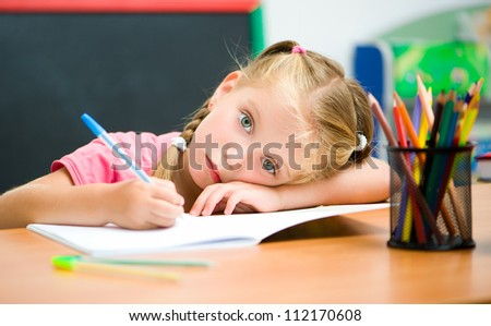 tired little girl at the desk with a pen
