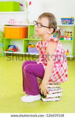 Tired little girl in glasses sitting on stack of books