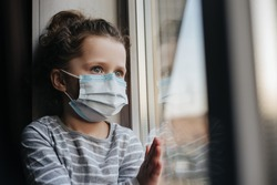 Tired little girl in medical sterile face mask sitting on sill looking at window, sad child spending time alone at home, upset pensive kid feeling lonely. Self isolation, home quarantine