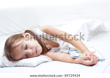 tired little girl sleeping, with hand on book, in the bed