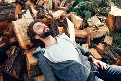 Tired lumberjack sleeping on pile of wood. Exhausted woodcutter having rest after hard work. Masculinity, manhood, handiwork, strength concept