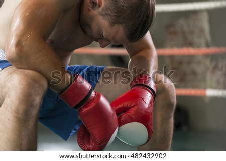 Tired male boxer sitting in the corner of the ring