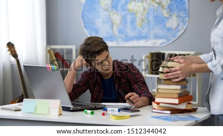 Tired male pupil looking at bunch of books in mother hands, distance education Foto stock ©