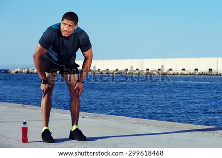 Tired male runner took a break after hard workout outdoors standing on sea and sky background with copy space area for your text message or information, sweaty sportsman having rest leaning on knees