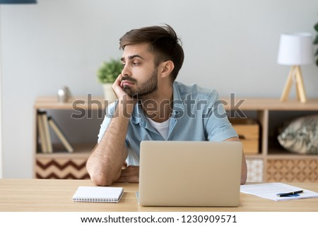 Tired male student or worker sit at home office desk look in distance having sleep deprivation, lazy millennial man distracted from work feel lazy lack motivation, thinking of dull monotonous job
