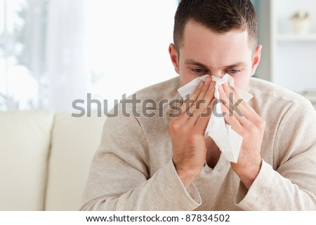 Tired man blowing his nose in his living room