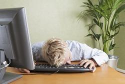 Tired man fallen asleep slumped over computer keyboard when working in office