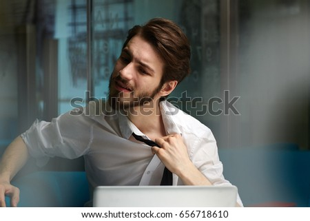 Tired man relieving his tie during late work in office