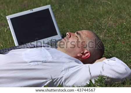 Tired man sleeping in a field near his laptop.