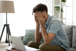 Tired man working at laptop massaging temples suffering from headache or migraine, exhausted millennial male sit on couch using computer having tension or blood pressure. Health problem concept