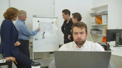Tired man works at the laptop, his workmates discuss scheme of apartement on desk