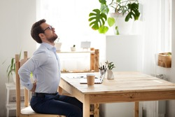Tired millennial office worker stretch in chair suffer from sitting long in incorrect posture, male employee have back pain or spinal spasm working in uncomfortable position. Sedentary life concept