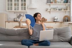 Tired millennial woman suffering from heatstroke flat without air-conditioner, waving blue fan, sitting on couch at home, working on laptop computer. Overheating, high temperature, hot summer weather.
