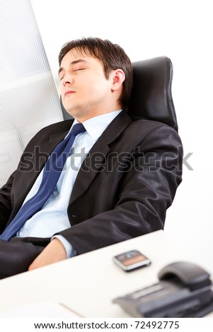Tired modern businessman sleeping on office armchair
