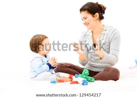 Tired mother and baby playing with toys.