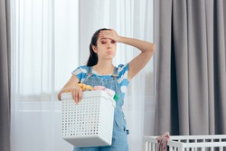 Tired Mother Holding a Basket of Dirty Laundry in Nursery Room. New mom feeling exhausted dealing with household chores