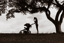 Tired mother suffering from postpartum depression. Stressed sad mother pushing stroller.