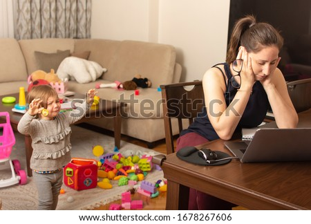 Photo of Tired mother trying to work on a laptop at home during her kid crying. Childcare and working mom concept. Women powerful. Toddler tantrum. Young lady working at home during quarantine.