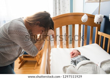 Tired Mother with Upset Baby Suffering with Post Natal Depression.