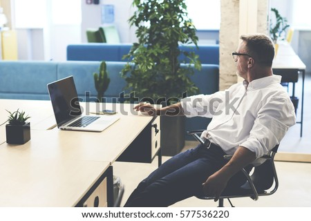 Tired of working in the office experienced employee sitting at the workplace with laptop while ponders on own business enterprise. Skilled mature CEO is pondering over ideas for new important project