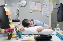 Tired office worker sleeping on a pillow on his office desk.