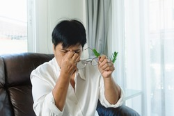 Tired old woman removing eyeglasses, massaging eyes after reading paper book. feeling discomfort because of long wearing glasses, suffering from eyes pain or headache
