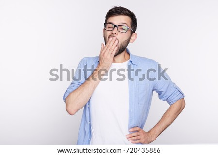 Tired or bored Caucasian hipster young man covering mouth while yawning, feeling exhausted after hard day at work. Handsome male student having sleepy boring look before the meeting he doesn't like.