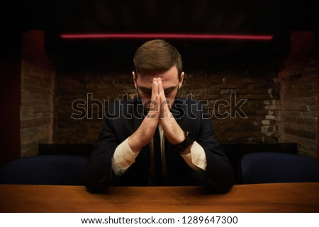 Tired or frustrated businessman with his hands put together by forehead bending over wooden table in restaurant
