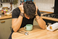 Tired or Sick Attractive Young Man with Eyes Closed and Hand in Hair, Leaning with Elbow on Kitchen Table and Holding Cup of Coffee, While Catching Up on Sleep