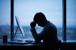 Tired or stressed businessman sitting in front of computer in office